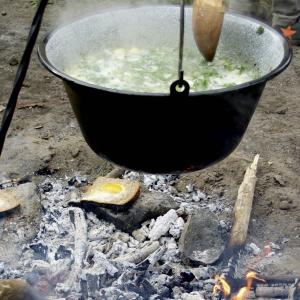 Gründonnerstagssuppe im Kessel und Ei im Brot vom heißen Stein